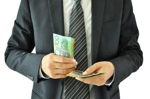 man-in-suit-counting-australian-money-resize-medium